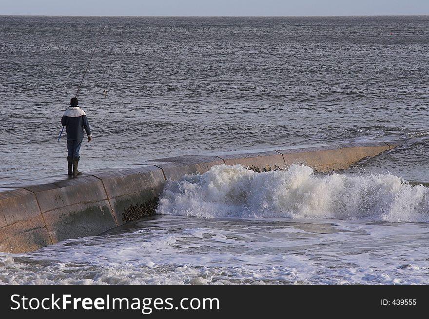 Man fishing on sea wall