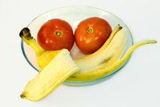 Banana With Tomatoes On Glass Plate Stock Photography