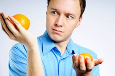 Free Man In A Shirt With Two Oranges Royalty Free Stock Photos - 4326038