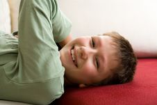 Happy Teenager Lie On Red Sofa Royalty Free Stock Photography