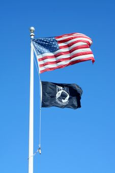 American And POW Flags Against A Blue Sky Stock Image