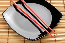Red Chopsticks And Black Dish On A Bamboo Mat. Stock Photo