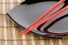 Free Red Chopsticks And Black Dish On A Bamboo Mat. V. Stock Image - 4368731