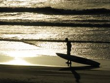 Silhouette With Board At Sunset Stock Photo