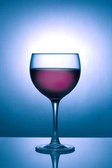 Glass Of Wine Silhouetted Against Blue Spotlight Royalty Free Stock Photography