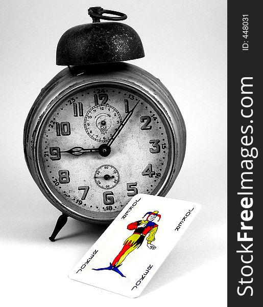Old clock and a joker card