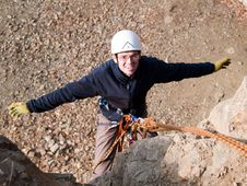 Climber Hanging On The Rock With Arms Wide Open Stock Image