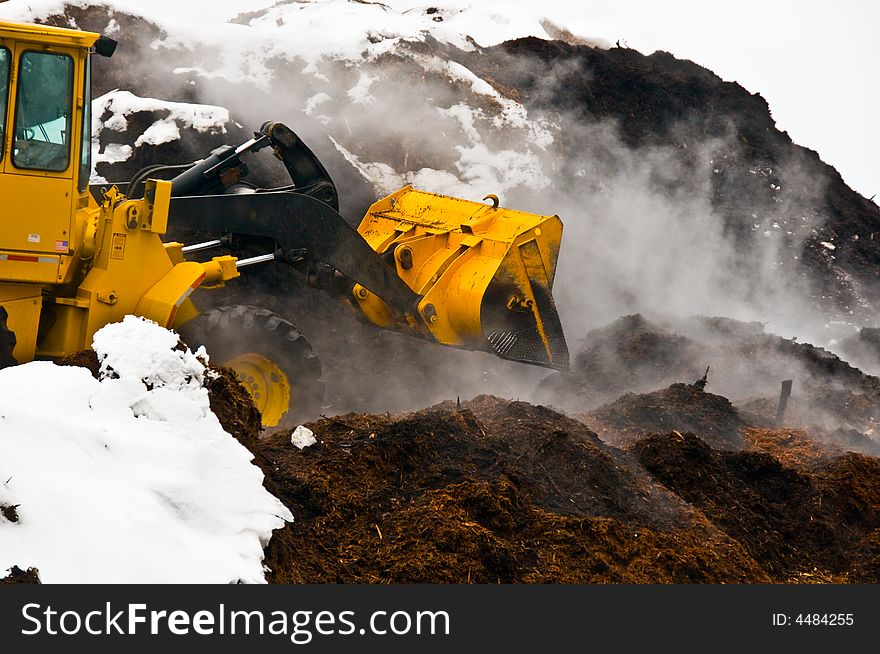 Action shot of front-end loader and mulch piles