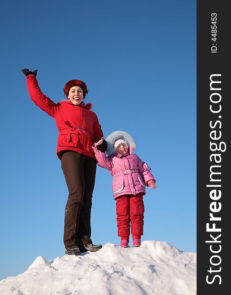 Mother and child stand on top of snowy hill