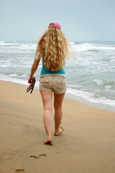 Free A Young Woman Walks Alone On The Beach Stock Images - 4519504