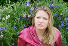 Pouting Woman In Flower Garden Royalty Free Stock Photography