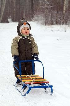 Baby Standing Near Sled Stock Image