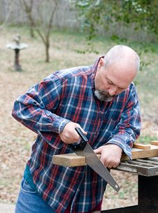 Free Man Cutting Board With Hand Saw Stock Photos - 4555053