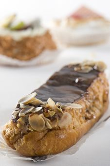 Chocolate Eclair. Cupcakes In Background. Royalty Free Stock Photography