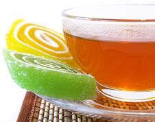 Multi-coloured Fruit Candy And Cup Of Tea Royalty Free Stock Image