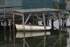 Small White Boat Under An Old Roof Royalty Free Stock Image