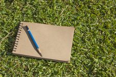 Free Notebook Lying On Green Grass Stock Image - 46230951