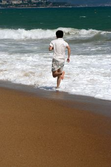Free A Man Running Along Beach With Ocean Waves Stock Photos - 4643973