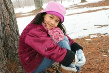 Nine Year Old Girl Sitting Outdoors In Winter Stock Photo