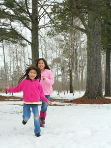 Two Girls Running Through The Snow Stock Photography