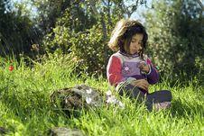 Girl Sitting In Grass Holding Flower Stock Images