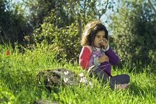 Free Girl Sitting In Grass Smelling Flower Royalty Free Stock Photography - 4657757
