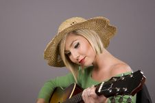 Blonde Playing Guitar In Straw Hat Royalty Free Stock Photos