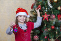Free Little Girl In Santa Hat Near Christmas Tree Stock Photography - 47483172