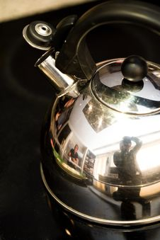 Free A Metal Tea Kettle On A Black Glass Stove Royalty Free Stock Image - 4752176