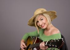 Blonde Playing Guitar And Smiling Royalty Free Stock Photography