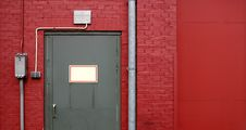 Free Grey Door On Red Wall Royalty Free Stock Image - 486186