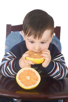 Free Small Boy Eats Fresh Grapefruit Stock Images - 4813654