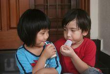 Girl And Boy Drinking Yogurt Stock Photography