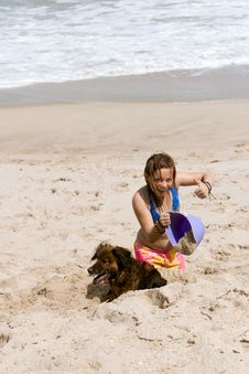 Girl In The Sand With Bucket And Dog Stock Photography
