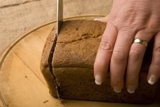 Free Woman Slicing Loaf Of Rye Bread Royalty Free Stock Photography - 4901027