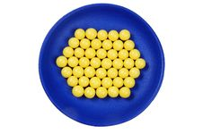 Blue Plateful Of Yellow Drops Vitamin Stock Photo