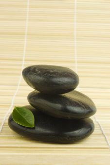 Free Black Zen Pebbles And Green Leaf On Bamboo Royalty Free Stock Photos - 4928768