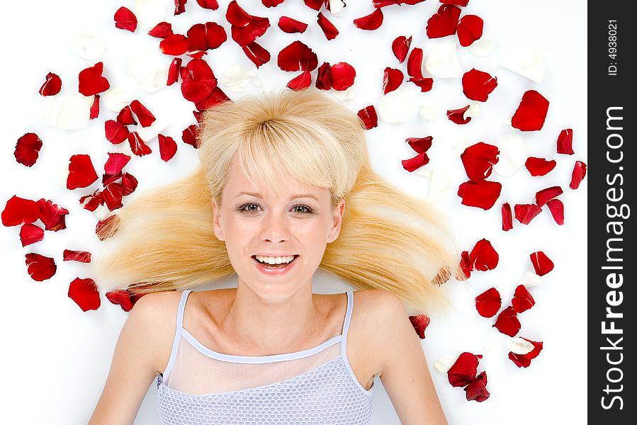 Beautiful young woman throwing rose petals