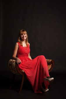 Young Beautiful Woman In Red Dress Sitting On A Chair Royalty Free Stock Photos