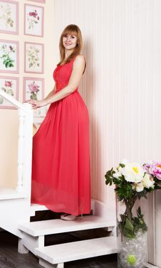 Young Woman In Red Dress Standing On The Stairs Royalty Free Stock Photography