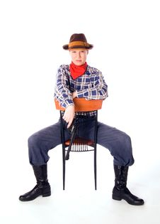 Cowgirl With Gun Siiting On Chair And Glares Down Royalty Free Stock Image