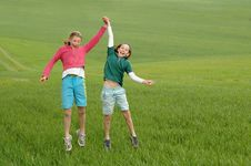 Free Girls Jumping In The Air In A Green Field Royalty Free Stock Photo - 5020795