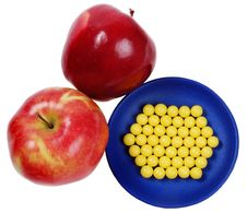 Blue Plateful Of Yellow Drops Vitamin And Red Appl Stock Images