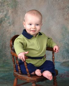 Happy Baby On Wooden Chair Royalty Free Stock Photography