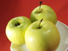 Three Green Apples On Red Stock Photo