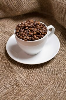 Cup With Freshly Roasted Coffee Beans On Sackcloth Stock Images