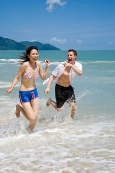 Free Couple Racing On The Beach Wit Stock Photo - 5083080