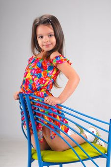 Little Girl Sitting On A Chair Stock Image