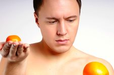 Man With Oranges Makes A Choice Royalty Free Stock Image