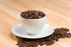 Free Cup With Coffee Beans On Hardwood Floor Royalty Free Stock Photo - 5120355